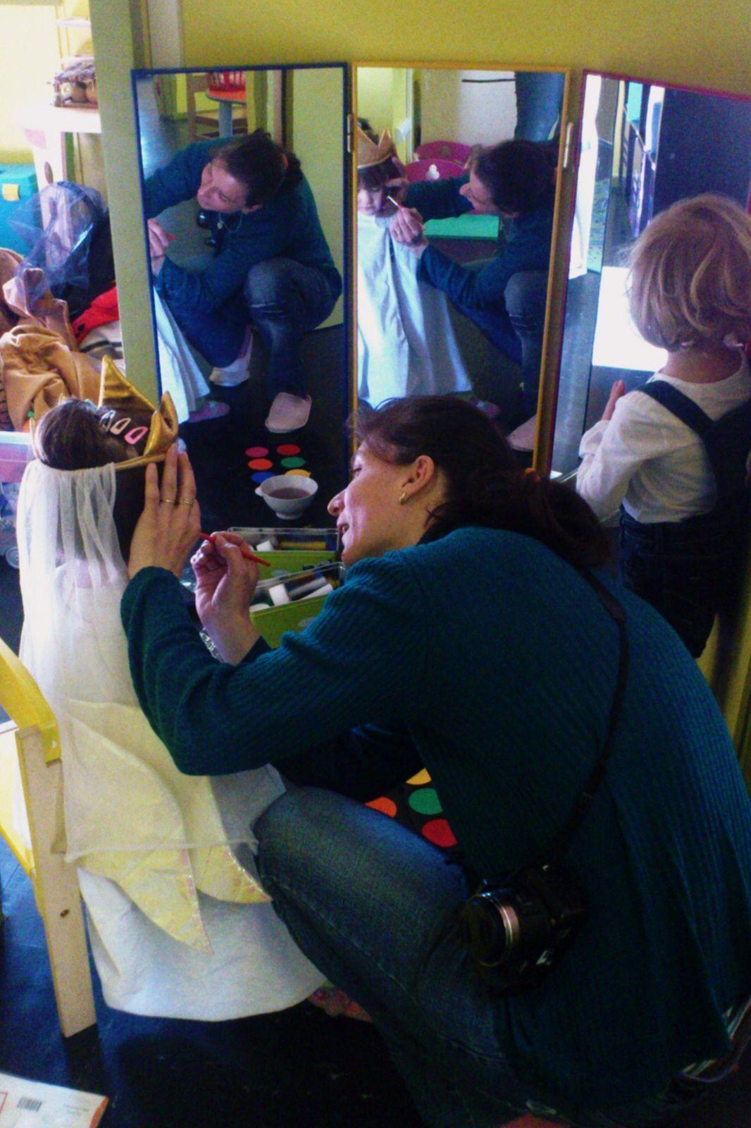 """Le coin maquillage est installé, à disposition des enfants et des adultes. Certains enfants ont préféré commencer par un petit pochoir sur la main, avant d'aller plus loin. Pour d'autres, un seul dessin sur la joue a suffi à les contenter. Le miroir est indispensable, pour suivre la """"transformation""""...Se maquiller les mains toute seule, au stick ou au pinceau, c'est aussi très plaisant !"""
