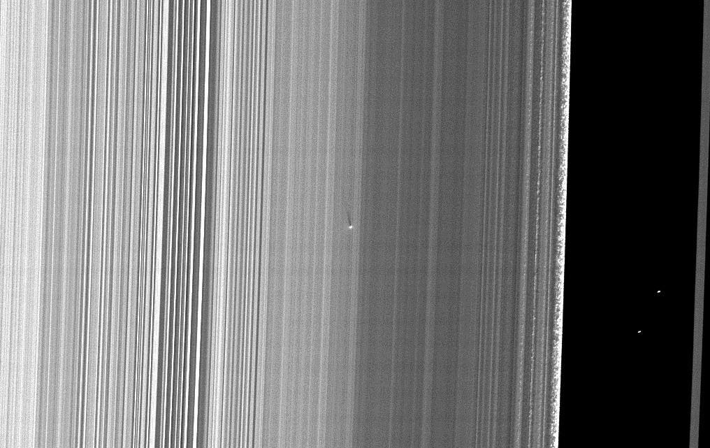 Quest'immagine, acquisita dalla sonda Cassini il 26 luglio 2009, permette di scorgere la lunga ombra proiettata da una piccolissima luna che si eleva di qualche centinaio di metri sopra il piano degli anelli. La scoperta di oggetti come questo è possibile solo quando gli anelli si trovano di taglio rispetto al Sole, cosa che rende massima la lunghezza delle ombre proiettate. Tale posizione corrisponde all'equinozio di Saturno, che si ripete all'incirca ogni quindici anni terrestri. L'ultimo equinozio di Saturno risale ad agosto 2009, pochi giorni dopo che Cassini ebbe inviato a Terra quest'immagine. I due punti luminosi visibili sulla destra sono stelle di sfondo, che appaiono allungate per via dello spostamento intercorso durante l'esposizione. Cortesia: NASA/JPL/Space Science Institute