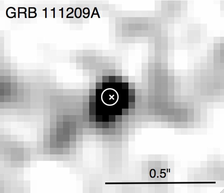 """La galassia ospite di GRB 111209A ripresa con la WFC3 del telescopio spaziale Hubble. Il cerchio sovrapposto indica la posizione del bagliore residuo dell'esplosione di raggi gamma con un margine di errore di 1 sigma. La 'x' marca il centroide della galassia otticamente determinato. <span class=""""di"""">Cortesia: arXiv:1302.2352v1 [astro-ph.HE]</span>"""