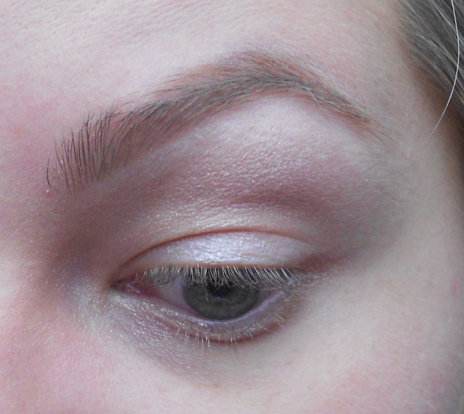 Avec un gros pinceau on prend un beige irrisé qu'on applique sous le sourcil.
