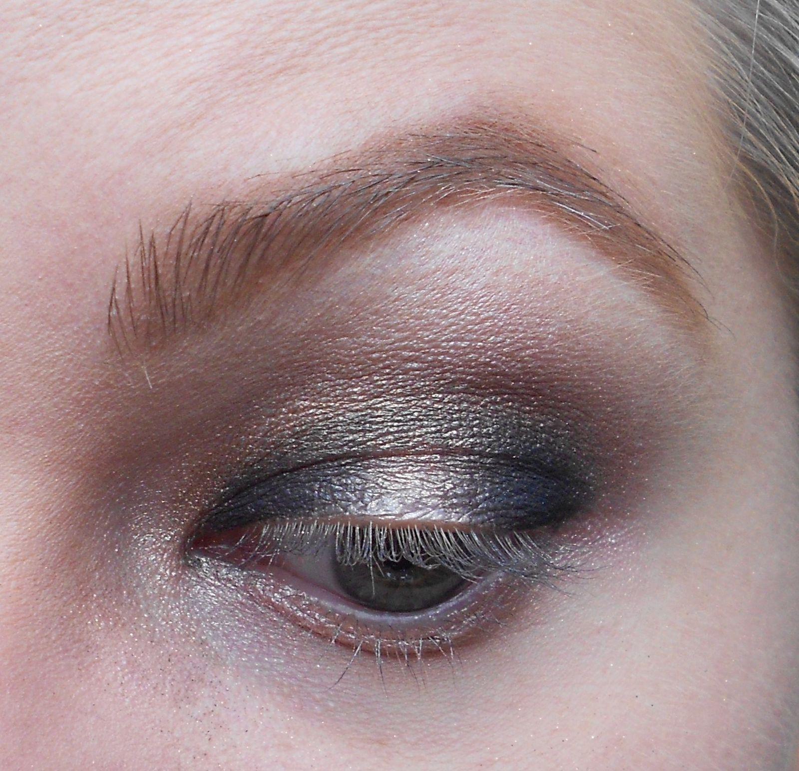 Avec un petit pinceau, on prend un noir qu'on va appliquer en coin interne et externe de la paupière mobile. Et également un peu dans le creux de l'oeil. Et on estompe bien le tout.