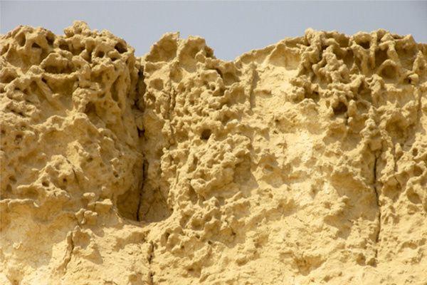 """Un bloc en haut du temple du Sphinx montrant une érosion tafoni intense et l'accumulation de sédiments granuleux et de dépôts d'alluvions qui ont affecté la surface supérieure du temple. Ce type d'érosion est unique à Giza et montre son age pré- antique. """"copyright:AntoineGigal2012"""""""