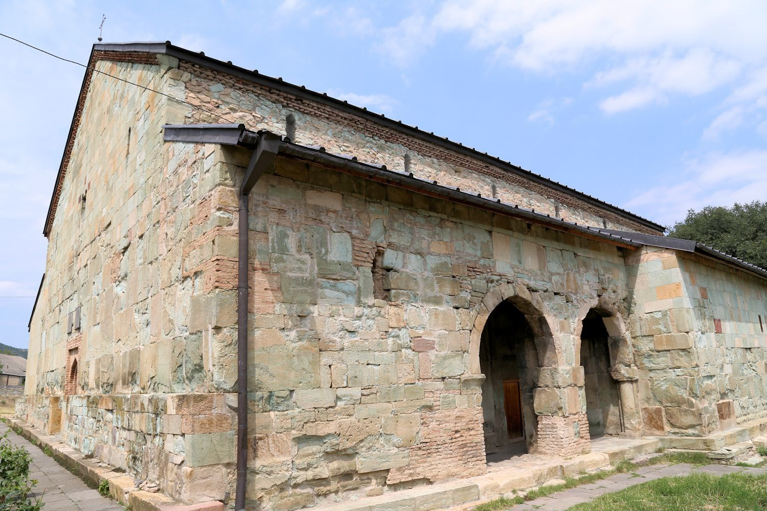The church looks simple and laconic. The walls are tiled with smooth rich turquoise tufa plates.