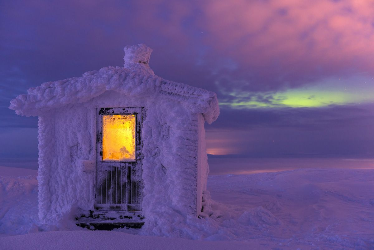 A Moment in Light Commended Gunar Streu (Germany)  Dundret nature reserve, Swedish Lapland  Hoarfrost-covered cabin at dusk, with Northern Lights in the background.