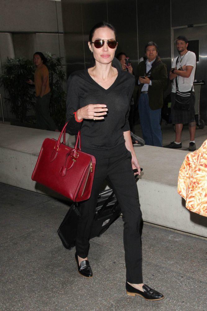 """4. Angelina Jolie """"non è solo moglie, mamma di 6 bambini, attrice, regista e filantropo. Angelina è sinonimo di stile classico, che si potrebbe definire """"alla Audrey Hepburn"""". Una classica scarpa bassa, un semplice maglione e pantaloni neri, di solito con una grande borsa che probabilmente contiene tutto ciò di cui ha bisogno per il viaggio, è il suo outfit per viaggiare."""""""