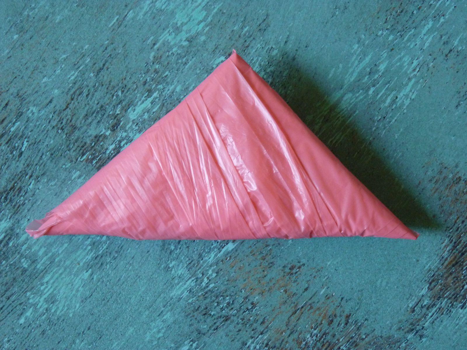 Ce triangle rose est un sachet plastique plié de telle façon qu'il ne prenne pas de place dans le sac. La méthode de pliage est japonaise. Ces sachets sont bien présents tout autour du globe. Merci de ne jamais les abndonner dans la nature!