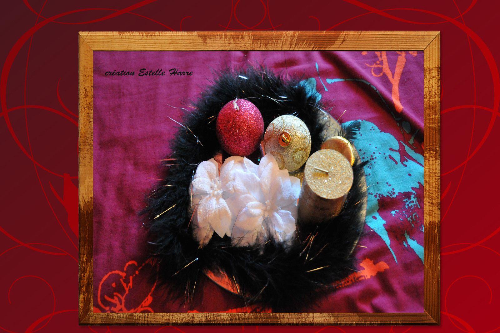 sur un miroir : bougies, boule, fleur de noël et boa noir