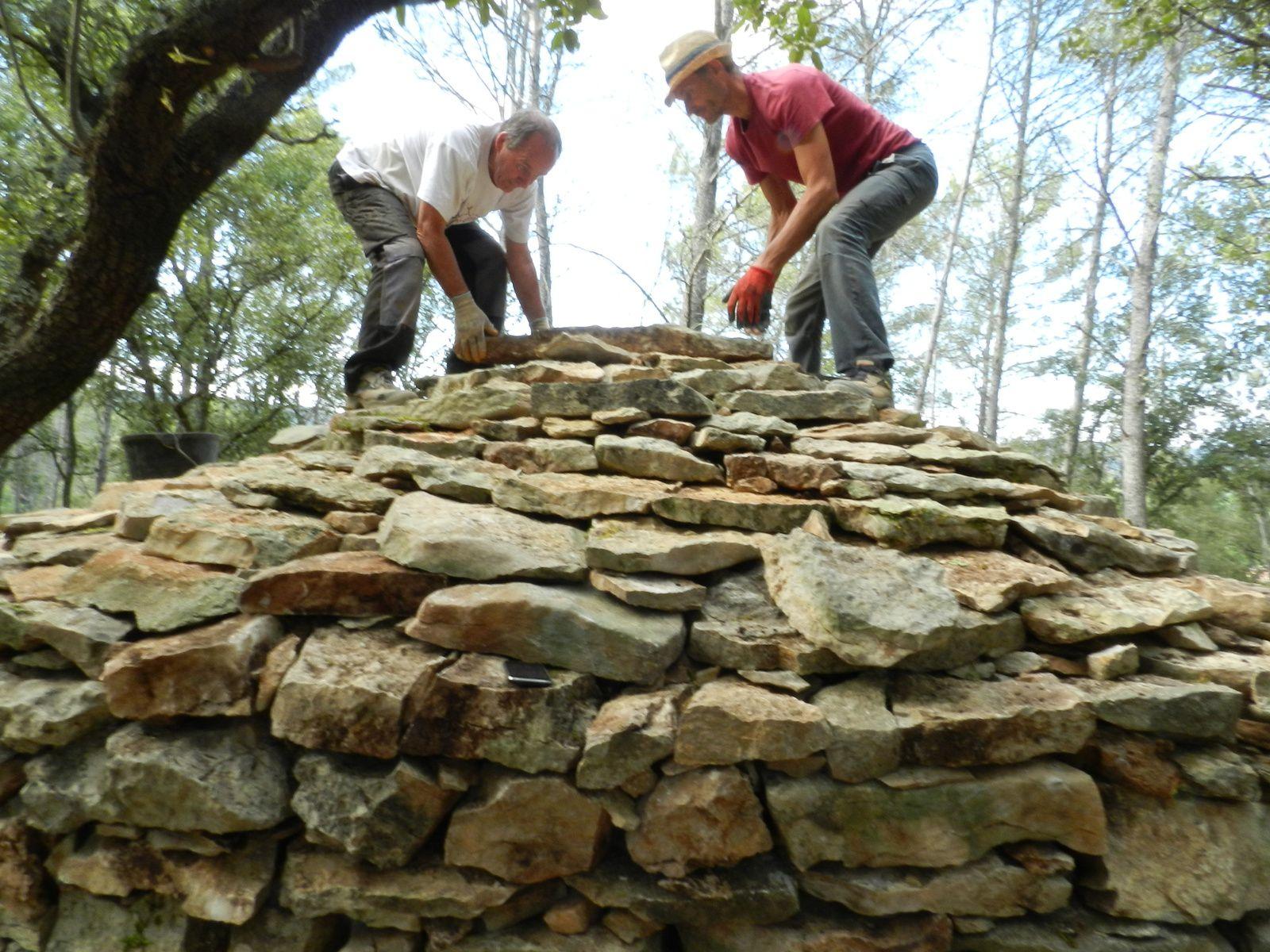Cette fois, on pose la dernière pierre. La cabane est restaurée.