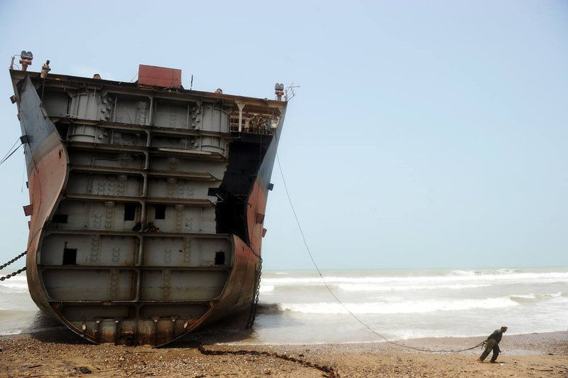 35/ In this photograph taken on July 10, 2012, a Pakistani worker pulls on a wire he will connect to a thick chain that will in turn be used to peel away a slab of the outer structure of a beached vessel in one of the 127 ship-breaking plots in Geddani, some 40Kms west of Karachi. Geddani's ship-breaking yards employ some 10,000 workers including welders, cleaners, crane operators and worker supervisors. The yards are one of the largest ship-breaking operations in the world rivaling in size those located in India and Bangladesh. It takes 50 workers about three months to break down a midsize average transport sea vessel of about 40,000 tonnes. The multimillion-dollar ship-breaking industry contributes significantly to the national supply of steel to Pakistani industries. For a six-day working week of hard and often dangerous work handling asbestos, heavy metals and polychlorinated biphenyls (PCBs), employees get paid about 300 USD a month of which half is spent on food and rent for run-down rickety shacks near the yards, a labour representative told AFP. AFP PHOTO / Roberto SCHMIDT/AFP/Getty Images
