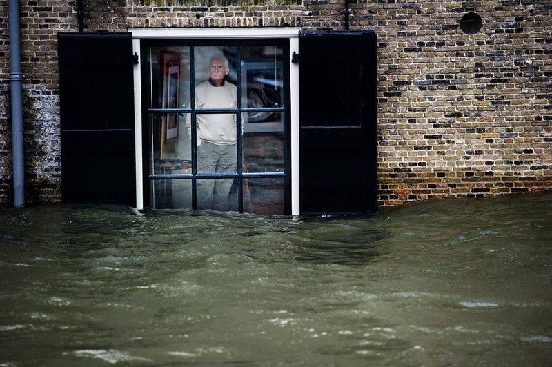 30/ A Dutch local resident, standing in his house, looks to high waters level through his window, in Dordrecht on January 5, 2012. Gale force winds reaching up to 110 kilometres (about 70 miles) an hour as well as heavy rains are expected along the Dutch coast. About a quarter of the country sits below sea level. ROBIN UTRECHT/AFP/Getty Images