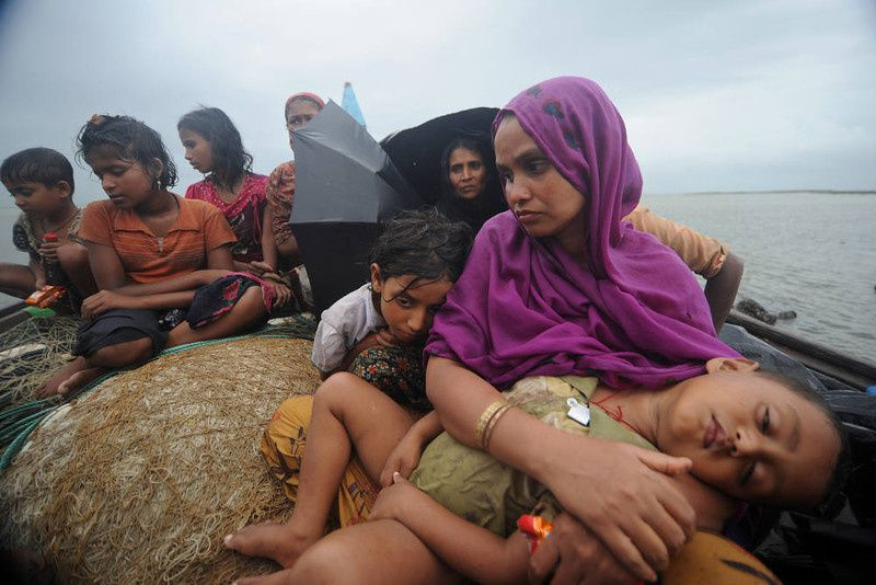 58/ Rohingya Muslims, trying to cross the Naf river into Bangladesh to escape sectarian violence in Myanmar, look on from an intercepted boat in Teknaf on June 13, 2012. Bangladesh on Wednesday refused three more boatloads of Rohingya Muslims fleeing sectarian violence in Myanmar, officials said, despite growing calls for the border to be opened. Bangladeshi guards have turned back 16 boats carrying more than 660 Rohingya people, most of them women and children, since June 11 as they tried to enter from neighboring Myanmar across the river Naf. AFP PHOTO/ Munir UZ ZAMAN/AFP/Getty Images
