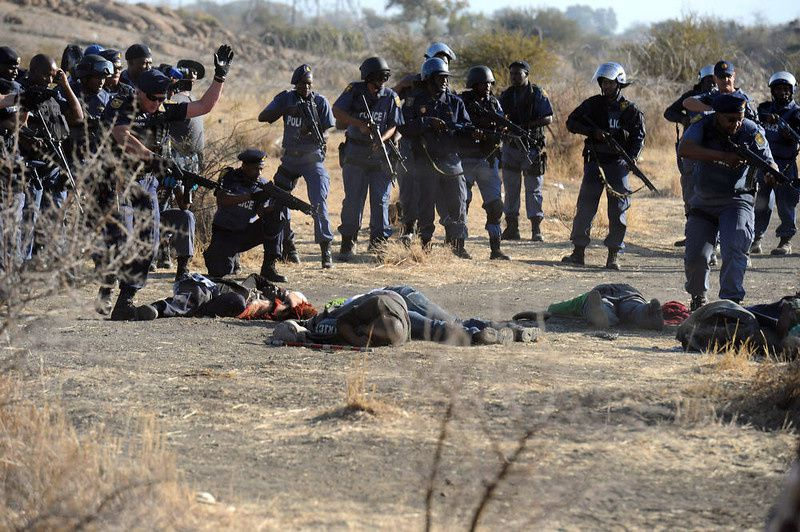 89/ Police surround fallen miners after they opened fire during clashes near a platinum mine in Marikana on August 16, 2012. Hundreds of workers armed with machetes, sticks and metal rods had gathered on a hillside near the mine, defying police orders to disperse. Several people were lying on the ground, some bleeding from wounds, after the crowd fled, according to an AFP reporter. AFP PHOTO-/AFP/Getty Images