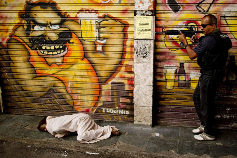 93/ A policeman secures the area before proceeding to pick up a child crack addict sleeping on the sidewalk at the entrance of the Jacare shantytown during an operation to clean the streets of crack addicts, in Rio de Janeiro, Brazil on September 12, 2012. AFP PHOTO/Christophe SIMON/AFP/Getty Images