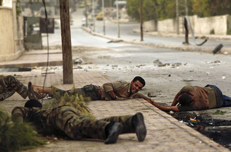 75/ Members of the Al-Baraa bin Malek battalion, part of the Free Syria Army's Al-Fatah brigade, duck to the ground as they pull a man (R) who was shot by a sniper twice in the Bustan al-Basha district of the northern city of Aleppo on October 20, 2012. Due to the risk of being shot by the sniper, no one was able to rescue the man who eventually ran towards rebels, only to be shot by the sniper a second time. Rebels then pulled him and rushed him to a hospital, though it is not known if he survived. Three civilians were shot on this main road in the space of three hours by the same sniper. AFP PHOTO/JAVIER Manzano/AFP/Getty Images