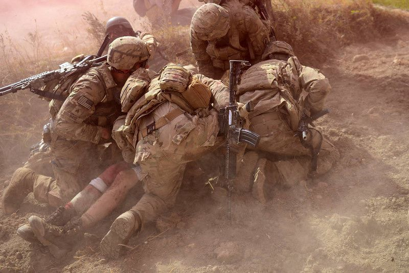 81/ US Army soldiers attached to 2nd platoon, C troop, 1st Squadron (Airborne), 91st U.S Cavalry Regiment, 173rd Airborne Brigade Combat Team operating under NATO sponsored International Security Assistance Force (ISAF) protect a wounded comrade from dust and smoke flares after an Improvised Explosive Device (IED) blast during a patrol near Baraki Barak base in Logar Province on October 13, 2012. The soldier, 21 year-old Private Ryan Thomas from Oklahoma suffered soft tissue damage and after surgery in Afghanistan was scheduled to be evacuated to Germany. After 11 years of war, 2,135 US soldiers dead, their Afghan colleagues turning on them, and widespread predictions the conflict will end in failure, coalition forces could be forgiven for suffering a dip in morale. But commanders and soldiers on the ground insist the challenges are bringing them closer together, even if the outcome of the war is uncertain and the perception of what constitutes success has changed. AFP PHOTO/ Munir uz ZAMAN/AFP/Getty Images