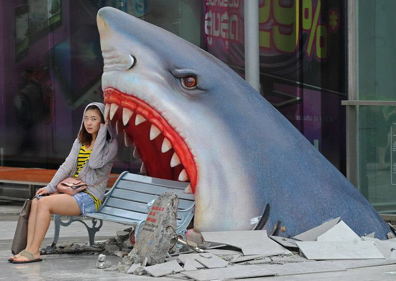 "11/ A foreign tourist sits next to a large art display of a shark displayed at a shopping mall in Bangkok on July 9, 2012. Thailand is a tourist magnet but its image as the ""Land of Smiles"" has been tested in recent years by deadly political unrest, devastating floods and more recently a bungled bomb plot involving Iranian suspects. AFP PHOTO / PORNCHAI KITTIWONGSAKUL/AFP/Getty Images"