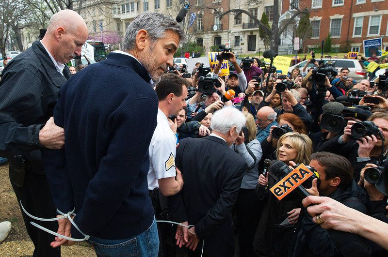 68/ Actor and activist George Clooney (2nd L) and his father journalist Nick Clooney (C) are arrested for trespassing upon the Sudanese Embassy in Washington, DC, on March 16, 2012. Clooney and his father were protesting against human rights abuses by the Sudanese government. AFP PHOTO/PAUL J. RICHARDS/AFP/Getty Images