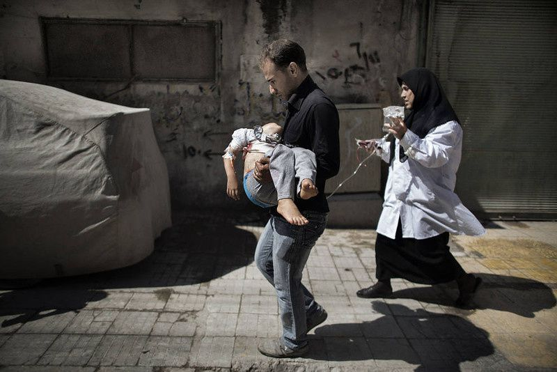 31/ A Syrian man carries his wounded daughter outside a hospital in the northern city of Aleppo on September 18, 2012. Syrian troops shelled several districts in Aleppo and clashed with rebels, as Damascus ally Iran proposed a simultaneous halt to the violence and a peaceful solution to the conflict. AFP PHOTO/MARCO LONGARI/AFP/Getty Images