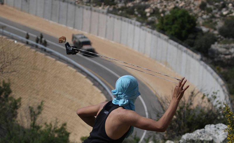 60/ A Palestinian youth readies to sling a stone at Israeli soldiers as they patrol along the controversial Israeli built separation barrier during clashes close to the village of Bilin, just west of the city Ramallah, in the occupied Israeli West Bank, on April 13, 2012. AFP PHOTO/ABBAS MOMANI/AFP/Getty Images