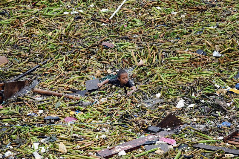 42/ A boy swims amongst the debris as he tries to salvage belongings from destroyed homes hit after two barges smashed into an informal settler area in Manila on July 30, 2012, when strong winds and rains due to Tropical Storm Saola hit the capital. At least one person was killed and millions were left without power on July 30, as Tropical Storm Saola brought heavy rains to large parts of the Philippines, the government said. AFP PHOTO / TED ALJIBE/AFP/Getty Images