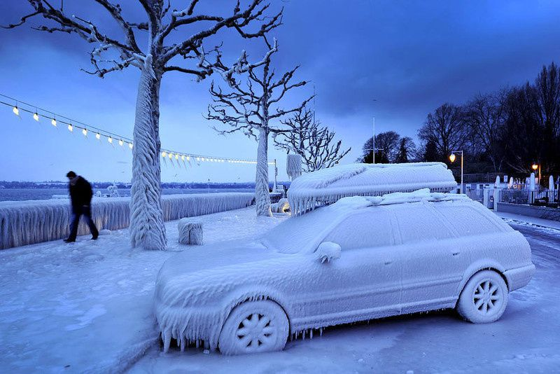 5/ A man walks past an ice covered car on the frozen waterside promenade at Lake Geneva in the city Versoix, near Geneva on early February 5, 2012. The death toll from the vicious cold snap across Europe has risen to more than 260, with the winter misery set to hit thousands of those seeking to escape it as air traffic was hit. AFP PHOTO / FABRICE COFFRINI/AFP/Getty Images