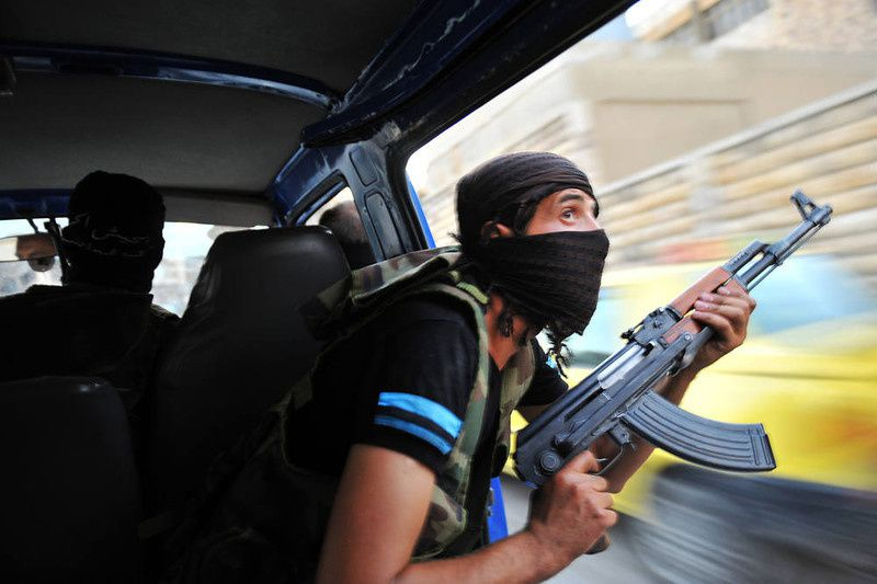 "16/ Syrian rebels hunt for snipers after attacking the municipality building in the city center of Selehattin, near Aleppo, on July 23, 2012, during fights between rebels and Syrian troops. Syrian rebels ""liberated"" several districts of the northern city of Aleppo on Monday, a Free Syrian Army spokesman in the country's commercial hub said. AFP PHOTO / BULENT KILIC/AFP/Getty Images"