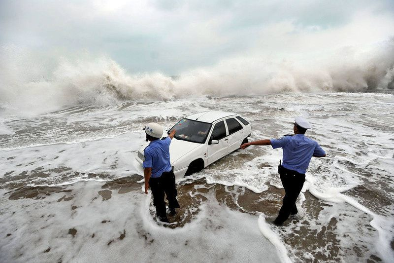 97/ This picture taken on August 28, 2012, shows police trying to help remove a car surrounded by water after its owner parked it on the bank to watch waves brought on by Typhoon Bolaven in Qingdao, in northeast China's Shandong province. Typhoon Bolaven -- the strongest storm to hit South Korea for almost a decade -- left a trail of death and damage in southwestern and south-central regions of the Korean peninsula on August 28, and crossed into China early on August 29. AFP PHOTOSTR/AFP/Getty Images