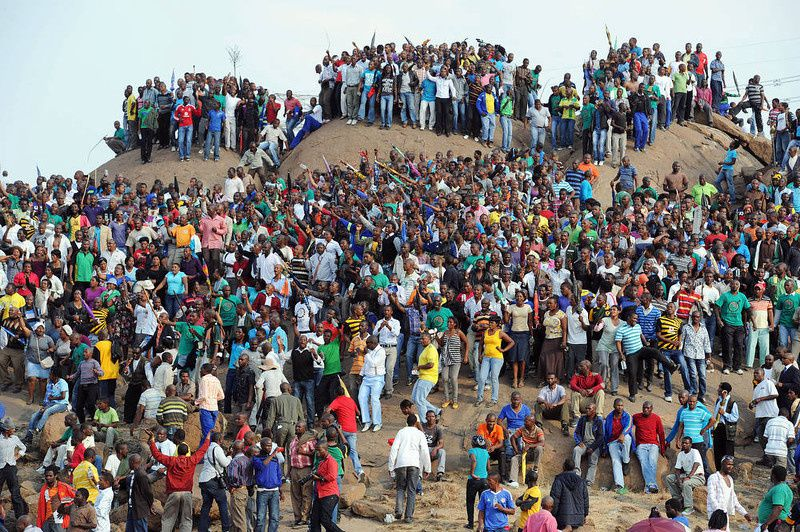92/ People gather on a hill in Marikana on August 23, 2012 after attending a memorial service for the 44 people killed in a wildcat strike at Lonmin's Marikana mine. Lonmin and nearby Impala Platinum closed for the day as workers prepared for memorials, including the main national service at Marikana where police gunned down 34 miners a week ago after deadly clashes had already claimed 10 people. The service at Lonmin will be the focal point during a day of mourning that will stretch across the country, as many of the victims were migrant workers whose bodies have already returned to their home villages. AFP PHOTO / STR-/AFP/Getty Images