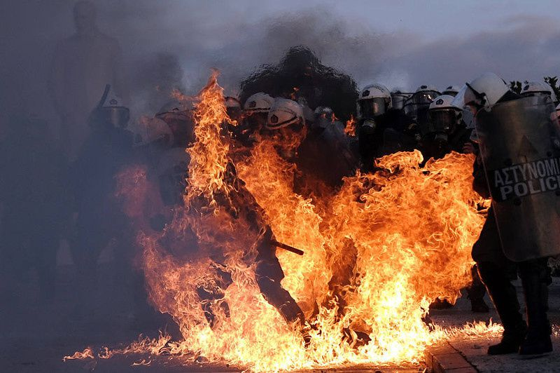 24/ A riot police is engulfed by flames during clashes with protestors in Athens on February 12, 2012. Greek police today used tear gas on petrol bomb-throwing protesters outside parliament where lawmakers were debating a new austerity plan aimed at staving off bankruptcy. AFP PHOTO / ARIS MESSINIS/AFP/Getty Images