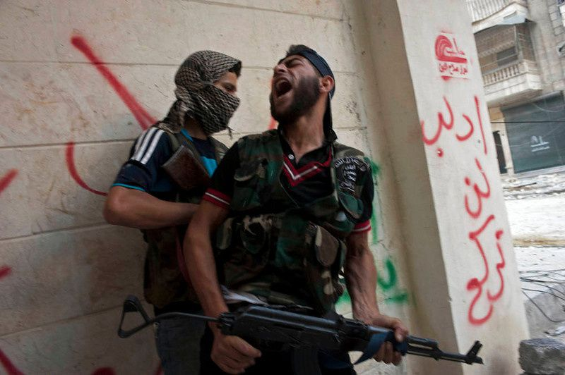 79/ Free Syrian Army fighters take cover as they exchange fire with regime forces in the Salaheddin neighbourhood of Syria's northern city of Aleppo on August 22, 2012. At least 12 people were killed in a raid on a district of Damascus, while fighter jets and artillery pummelled the city of Aleppo and rebels claimed seizing parts of a town on the Iraqi border, a watchdog said. AFP PHOTO / JAMES LAWLER DUGGAN/AFP/Getty Images