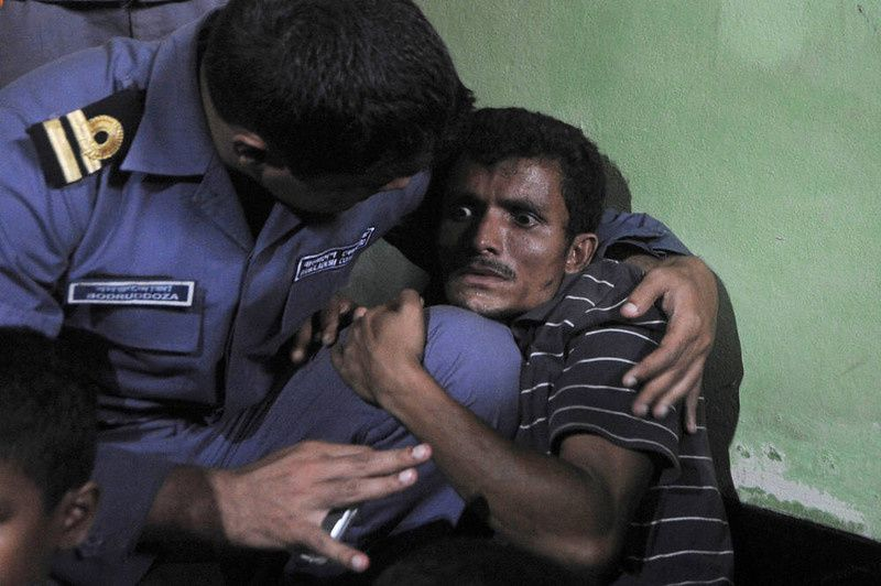 55/ A Rohingya Muslim from Myanmar (R), who tried to cross the Naf river into Bangladesh to escape sectarian violence, cries near his family in a Bangladeshi Coast guard station in Teknaf on June 19, 2012, before being sent back to Myanmar. Bangladesh is coming under increasing international pressure to open its border to Rohingya's fleeing the violence, but has so far refused to do so. AFP PHOTO/ Munir uz ZAMAN/AFP/Getty Images
