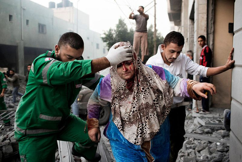 38/ A Palestinian woman is helped by a paramedic out of her building, damaged during an Israeli air raid on a nearby sporting centre in Gaza City November 19, 2012. Israeli air strikes on Sunday killed 31 Palestinians in the bloodiest day so far of its air campaign on the Gaza Strip, as diplomatic efforts to broker a truce intensified. AFP PHOTO/MARCO LONGARI/AFP/Getty Images