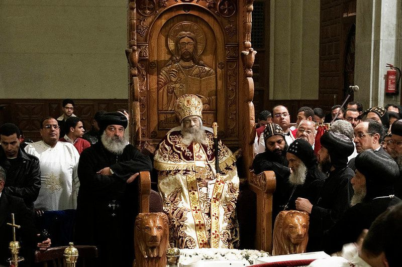 67/ Egyptian Coptic priests gather around the body of Pope Shenuda III, the spiritual leader of the Middle East's largest Christian minority, sitting dressed in formal robes on a wooden throne at the Saint Mark's Coptic Cathedral in Cairo's al-Abbassiya district on March 19, 2012. Pope Shenuda died at the age of 88, after a long battle with illness and based on his wishes he will be buried on March 20, at St. Bishoy monastery in Wadi Natrun in the Nile Delta where he spent his time in exile after a dispute with late president Anwar Sadat.AFP PHOTO/GIANLUIGI GUERCIA/AFP/Getty Images