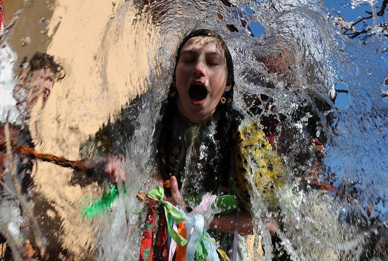 61/ Young Slovaks dressed in traditional costumes throw a bucket of water at a girl as part of Easter celebrations in the village of Trencianska Tepla, 145 km north of Bratislava on April 9, 2012. Slovakia's men splash women with water and hit them with a willow to symbolize youth, strength and beauty for the upcoming spring season.AFP PHOTO/SAMUEL KUBANI/AFP/Getty Images