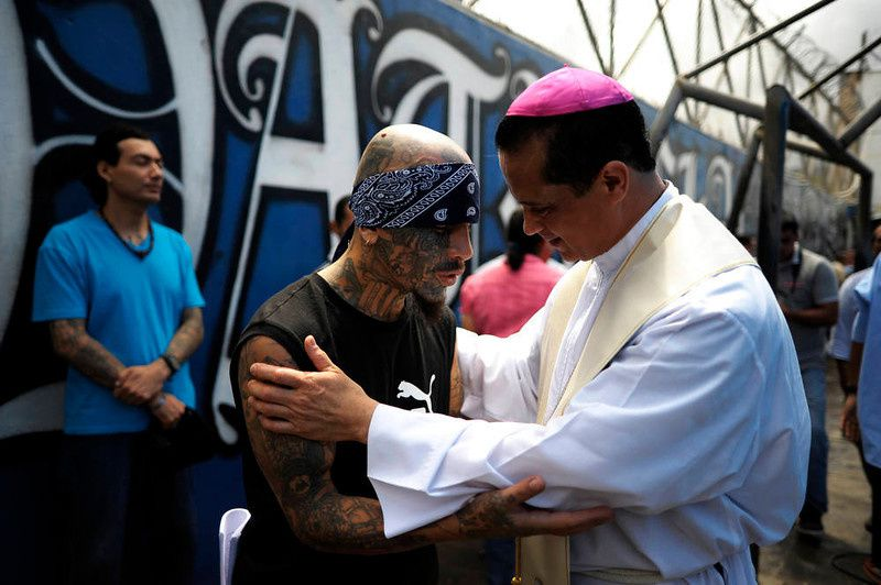 64/ Catholic priest Fabio Colindres (L) speaks with a member of Mara Salvatrucha gang during a mass at the prison of Ciudad Barrios, 160 km east of San Salvador, El Salvador on June 19, 2012. Inmates participated in a mass to celebrate 100 days after a truce was declared between gangs and the Salvadorean goverment. AFP PHOTO/ Jose CABEZAS/AFP/Getty Images