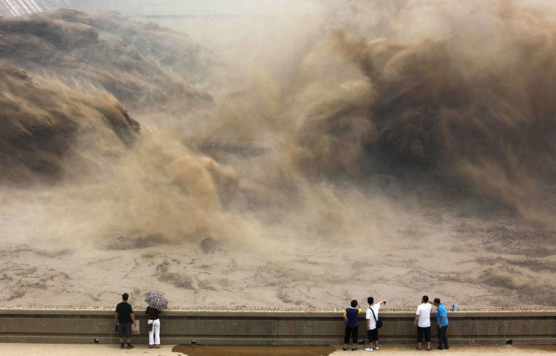 51/ This picture taken on July 6, 2012 shows visitors gathering to giant gushes of water released from the Xiaolangdi dam to clear up the sediment-laden Yellow river and to prevent localized flooding, in Jiyuan, central China's Henan province. China is hit by big downpours every summer often causing fatalities as seen in 2010, which saw the nation's worst flooding in a decade leaving more than 4,300 people dead or missing. AFP PHOTOSTR/AFP/Getty Images
