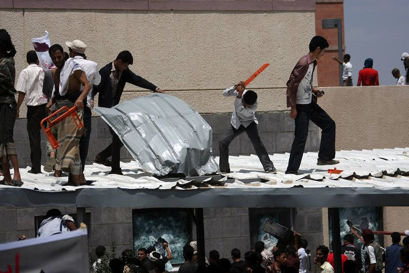 28/ Yemeni protesters try to break through the US embassy in Sanaa during a protest over a film mocking Islam on September 13, 2012. Yemeni forces managed to drive out angry protesters who stormed the embassy in the Yemeni capital with police firing warning shots to disperse thousands of people as they approached the main gate of the mission. AFP PHOTO/MOHAMMED HUWAIS/AFP/Getty Images
