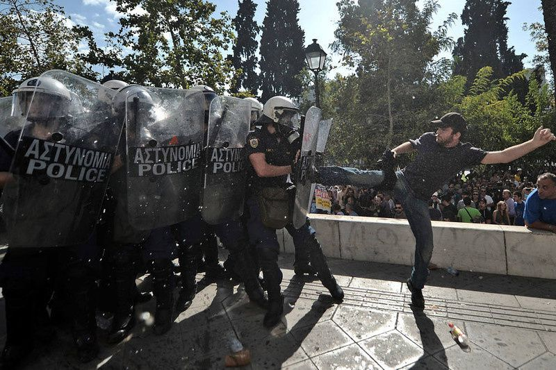 77/ A demonstrator clashes with riot police during a 24-hour strike in Athens on October 18, 2012. Greek riot police fired tear gas to disperse protesters at an anti-austerity rally in Athens held during a national general strike as EU leaders were to tackle the eurozone crisis at a summit. The protesters had broken through a police line outside luxury hotels on central Syntagma Square and scattered groups of youths later attacked police with stones and firebombs, an AFP reporter said. AFP PHOTO / ARIS MESSINIS/AFP/Getty Images