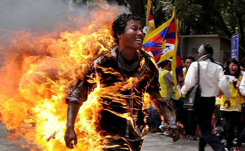 2/ Tibetan exile Jamphel Yeshi, 27, runs as he is engulfed in flames after he set himself on fire during a protest in New Delhi on March 26, 2012. A Tibetan exile set himself on fire on Monday during a rally in New Delhi to protest against an upcoming visit to India by Chinese President Hu Jintao, police said. AFP PHOTO/STmSTRDEL/AFP/Getty Images