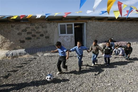 Children of the Jahalin Bedouin community play in the yard outside their school, which is made out of car tyres and mud, in the West Bank near Jerusalem December 1, 2009.  REUTERS/Mohamad Torokman