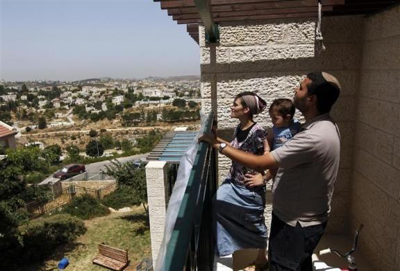 Yiska (L) and Yoel Fattal stand with their son on their balcony during an interview with Reuters in the Ulpana neighbourhood of the Beit El area near the West Bank city of Ramallah June 14, 2012.  REUTERS/Ronen Zvulun
