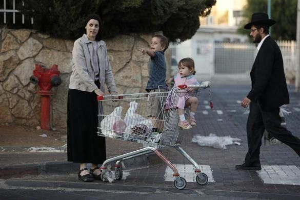 An ultra-Orthodox Jewish woman waits with her children outside a supermarket in the West Bank Jewish village of Modiin Illit September 14, 2010.  REUTERS/Nir Elias