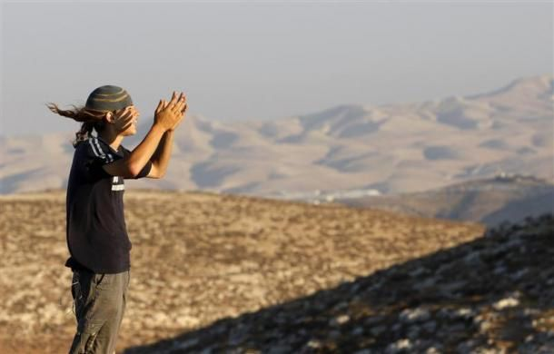 "A Jew prays in the new unauthorised outpost of ""Inbalim"", close to the West Bank city of Ramallah, July 27, 2009.  REUTERS/Gil Cohen Magen"