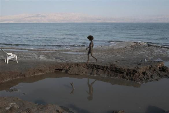 A boy covered with mud walks on the shore of the Dead Sea near the West Bank Jewish yichouv of Mitzpe Shalem February 27, 2011.  REUTERS/Baz Ratner