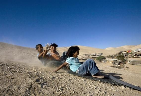 Palestinian bedouin children slide down a hill on a makeshift sled south of the West Bank Jewish yichouv of Mishor Adumim in the Judean Desert August 19, 2009.  REUTERS/Ronen Zvulun
