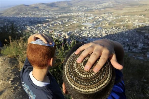 Jewish boys hold on to their skullcaps during a gust of wind, after a march from Har Bracha village to a lookout point on Mount Gerizim, overlooking Joseph's Tomb and the West Bank city of Nablus May 31, 2011.