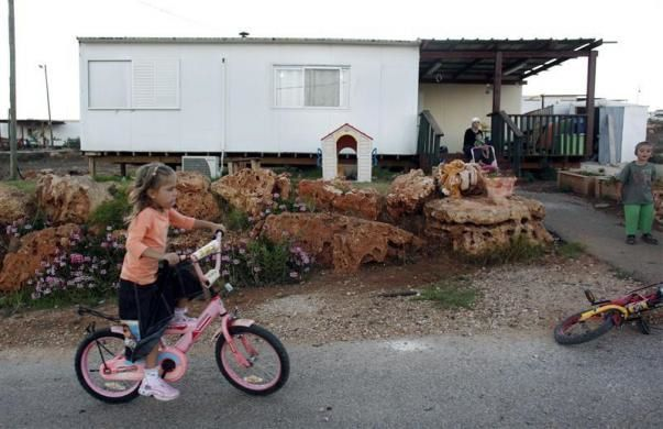A girl rides her bicycle outside her home in the West Bank Jewish yichouv of Kida August 31, 2010.  REUTERS/Nir Elias