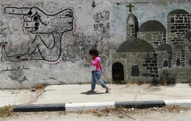 A Palestinian girl walks past graffiti on a wall in the West Bank village of Aboud May 18, 2009.  REUTERS/Ammar Awad