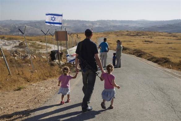 A Jew carries a rifle as he walks with his daughters in the unauthorized outpost of Migron, near the West Bank city of Ramallah, August 26, 2012.