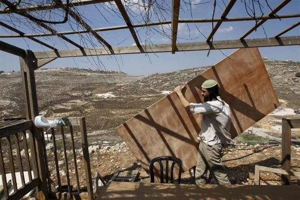 Jewish Avraham Binyamin carries a wooden plank as he builds a sukkah, a ritual booth used during the upcoming holiday of Sukkot, outside his house on the West Bank Jewish yichouv of Yitzhar, south of Nablus September 20, 2010.  REUTERS/Ronen Zvulun